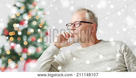 old age, holidays, problem and people concept - senior man in glasses thinking at home over christmas tree background and snow