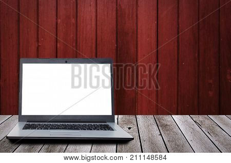 laptop computer with blank screen for presentation on wooden desk and old wooden wall background advertising commercial marketing technology internet and business concept
