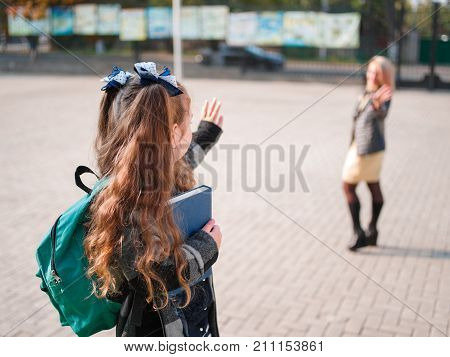 A girl goes to school saying goodbye with a green briefcase and books