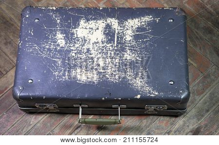 Old shabby suitcase on latches on a wooden floor