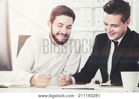 Two young business partners are working together while sitting at their table in a white office. Toned image