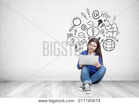 Portrait of a smiling teen girl with long dark hair wearing blue jeans and a shirt and holding her laptop while sitting on the floor near a concrete wall with an internet search sketch on it. Mock up