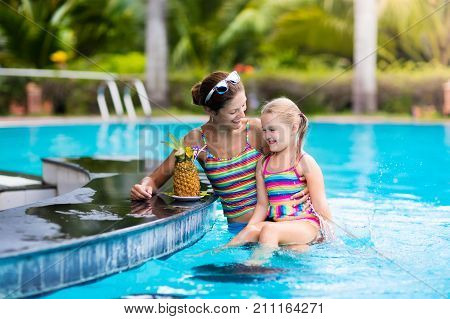 Child and mother drink juice in swimming pool bar. Summer family vacation with kids. Little girl holding fresh pineapple cocktail in beach cafe. Kid swim with tropical fruit lemonade in luxury resort.