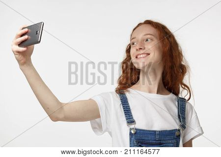 Photo Of Beautiful Young Redhead Female Isolated On Grey Background, Stretching Arm With Smartphone