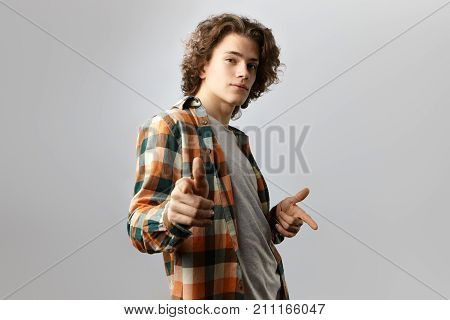 Cool stylish guy wearing fashionable checkered shirt over grey top staring at camera with confident joyful smile and pointing both index fingers at you. Handsome young man dancing in studio