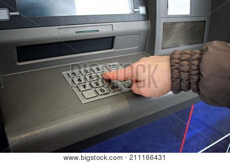 Close up of hand entering pin at an ATM. Female arms ATM - entering pin.Woman using banking machine.