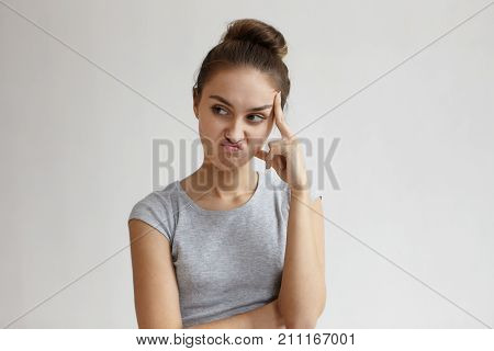 Thoughtful pensive young woman with hair bun making displeased grimace as if saying No that's not an option while trying to solve problem thinking over decision holding head and looking sideways