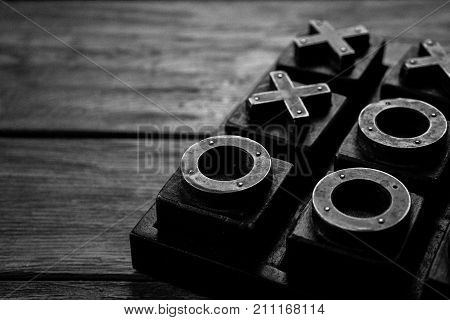 Close up of Tic Tac Toe Noughts and crosses X and O game isolated on a wooden table black and white