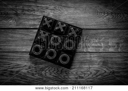 Tic Tac Toe Noughts and crosses X and O game isolated on a wooden table black and white