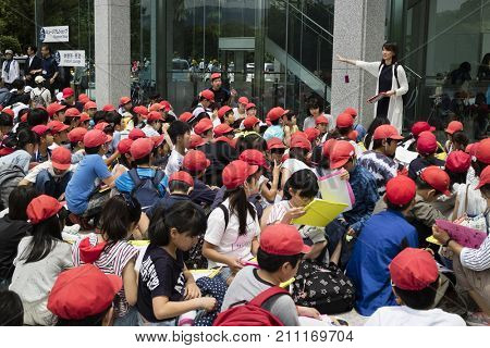 Hiroshima, Japan - May 25, 2017: Group of students sitting in front of the Hiroshima Peace Memorial Museum in Peace Memorial Park