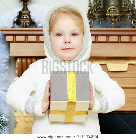 A sweet little four year old girl with a gift in her hands on Christmas Eve.