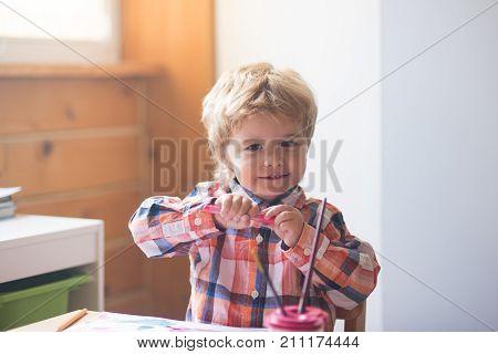 Kid draws pink felt-tip pen and watercolor paints. Happy little artist paints a painting of bright colors children's art art therapy. Talented preschooler painter
