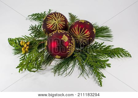 3 maroon Christmas ornaments with gold stars and starbursts on a bed of White Pine and Cedar boughs