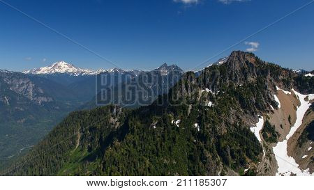 A landscape view of Chokwich Peak, Bedal Peak, Glacier Peak and other neighboring mountains taken from an overlook along Mount Forgotten hiking trail.