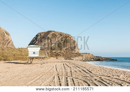 A lifeguard tower at Point Mugu State Park on the Pacific Coast Highway in Malibu, California with Mugu Rock in the background.