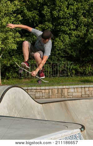 ATLANTA, GA - JULY 2017:  A teenage boy completes a skateboard trick as gets airborne exiting the concrete bowl at the Old Fourth Ward Skateboard Park in Atlanta GA on July 2 2017.