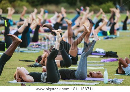 ATLANTA, GA - JULY 2017: Dozens of people do a yoga pose lying on their backs as they take part in a free group yoga class at the Old Fourth Ward Park in Atlanta GA on July 2 2017.