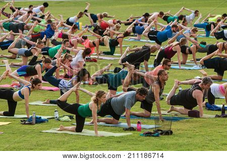 ATLANTA, GA - JULY 2017: Dozens of people grab their right leg and stretch as they take part in a free group yoga class at the Old Fourth Ward Park in Atlanta GA on July 2 2017.