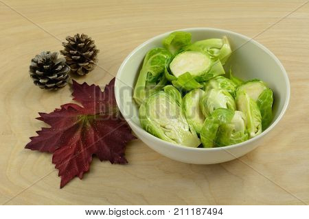 Brussel sprouts in white bowl tossed in olive oil in preparation for grilling or roasting