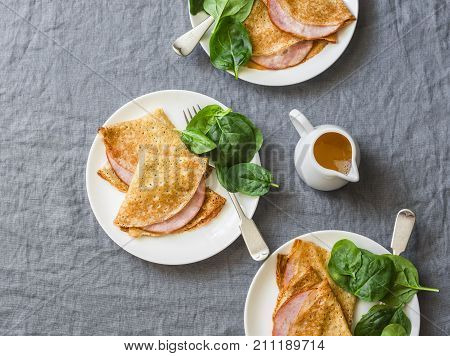 Crepes with ham and spinach. Delicious nourish breakfast on a grey background top view
