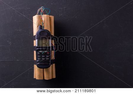 Bomb with explosives and detonator phone. The denamite sticks are connected by wires with a phonemon. Terrorism. Black background. Copy space for text