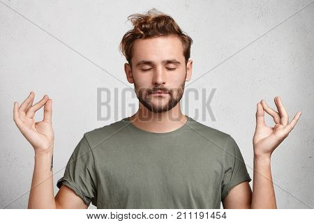 Concentrated Bearded Man With Appealing Appearance Meditates Against White Background, Tries To Rela