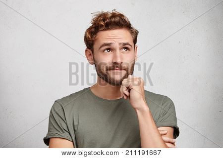 Portrait Of Pensive Pleasant Looking Young Male With Beard And Mustache, Keeps Hand Under Chin, Look