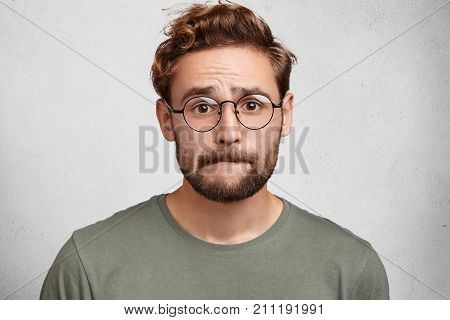 Worried Bearded Guy In Eyewear, Bites Lower Lip, Anticipate Important Decision Or Feels Nervous Befo