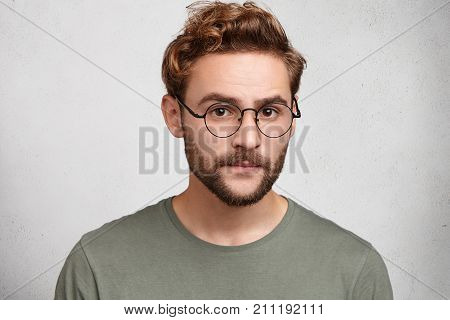 Headshot Of Serious Clever Man Professor Going To Conduct Lecture, Wears Spectacles, Waits Students.