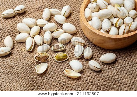 Bowl with pistachios on a wooden table with sacking.Roasted salted pistachio nuts healthy delicious food