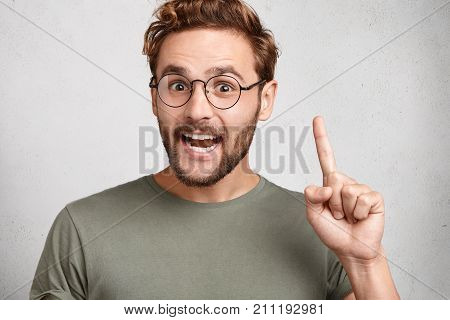 Young Happy Man Gets Good Idea, Raises Fore Finger As Going To Voice It, Being Glad Have Genius Thou