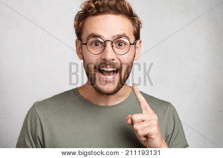 I Have Got Brilliant Idea. Smart Caucasian Cheerful Man With Beard And Mustache, Raises Index Finger