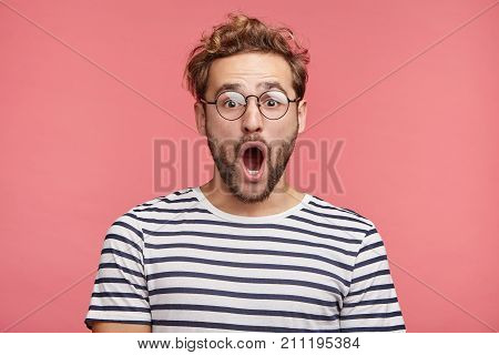 Indoor Shot Of Stupefied Handsome Male Opens Mouth Widely, Wears Striped T Shirt, Has Shocked Expres
