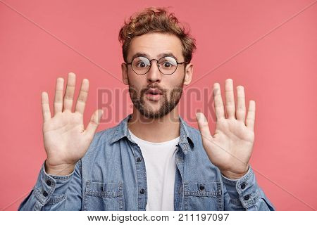 I Give Up! Attractive Unshaven Stylish Man Shows Palms, Demonstrates His Innocence, Surrenders, Isol