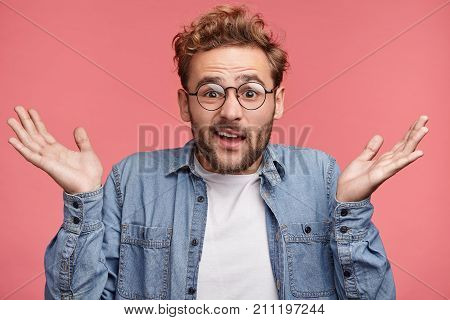 Waist Up Portrait Of Confused Young Man With Trendy Hairdo And Stubble Wears Demin Shirt And Round S