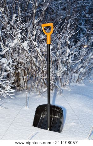Shovel in the snow in the night forest