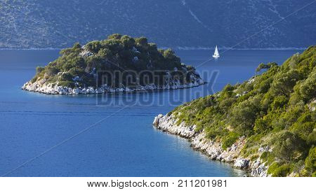 Sailboat and an islet in the Molos Gulf in Ithaca island, Greece.