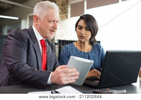 Frowning concentrated business team discussing electronic document on tablet. Senior businessman showing report at meeting. Doubt concept
