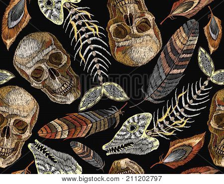 Feathers fish bone and indian skull embroidery seamless pattern. Beautiful feathers of tropical birds skeleton of fish and human skull classic embroidery seamless pattern