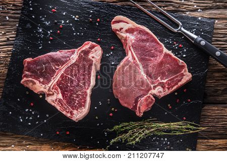 Beef Steak T-bone. Raw Beef Steak T-bone On Slate Board With Salt Pepper Herbs  Butcher And Fork