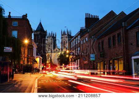 York UK. Sundown of central York UK with York Minster cathedral on the back and blue cloudy sky. Car traffic trail lights in York UK