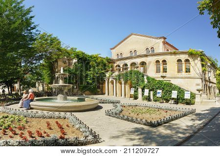 Tourists At The Fountain And The Flower Gardens Around The Museum Building With The Byzantine Exhibi