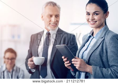 Positivity is the key to success. Selective focus on a young lady in formal attire holding her digital tablet with two hands and beaming into the camera while standing next to her cheerful colleague.