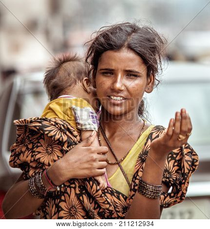 New Delhi India - August 14 2016: Young indian beggar woman with baby begs the alms in New Delhi India