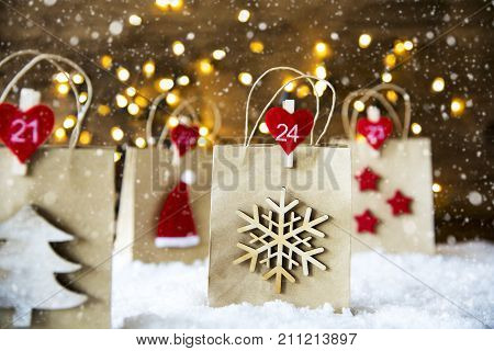 Christmas Shopping Bag With Numbers 21 to 24 On Snow. Decoration Like Santa Claus Hat, Snowflake, Christmas Tree And Stars. Fairy Lights In Background. Snowy Scenery With Snowflakes