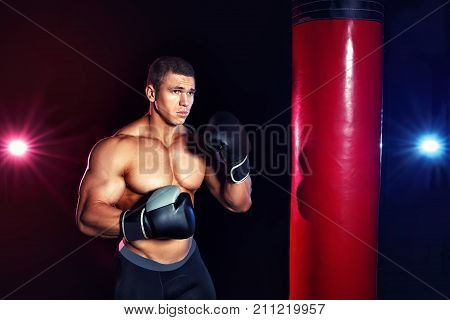 Muscular man boxing punching bag in gym. Power fitness man with boxing gloves posing at the camera. Sport, fitness, boxing concept