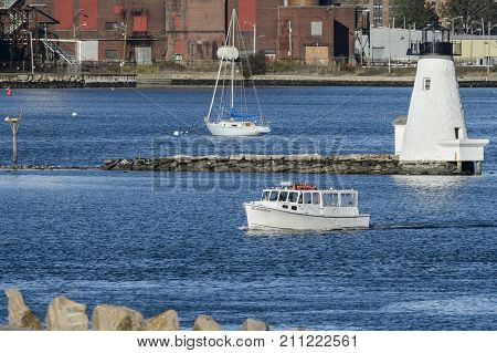 New Bedford Massachusetts USA - October 27 2017: Seahorse Cuttyhunk Water Taxi passing Palmer's Island Lighthouse in New Bedford harbor