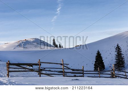 Winter rural background with small wooden alpine house, pines, fence, snow field, mountains, blue sky, Transylvania