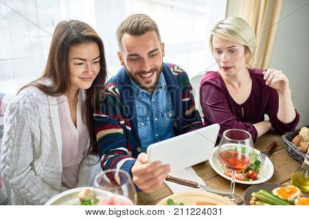 Portrait of three young people smiling happily video chatting from difital tablet at dinner table during holiday celebration