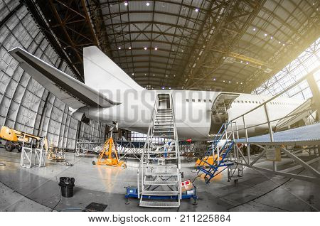 Large Passenger Aircraft On Service In An Aviation Hangar Rear View Of The Tail, Gangway Ladder Entr